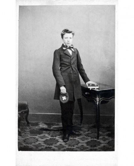 Jeune homme debout, une main sur un livre, l'autre tenant sa casquette à croix blanche