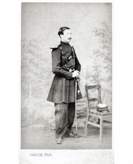 Militaire moustachu debout tête nue, appuyé sur son sabre (gants et képi posés)