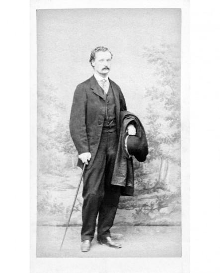 Homme moustachu debout , tenant canne, chapeau melon et manteau