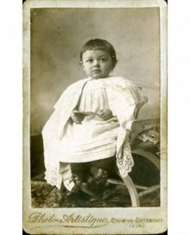 Enfant en robe et cape de dentelle assis