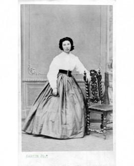 Femme en jupe et corsage debout, accoudée à une chaise