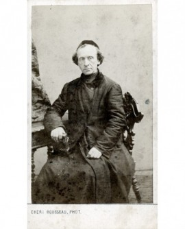 Ecclésiastique en calotte, assis, bréviaire à la main