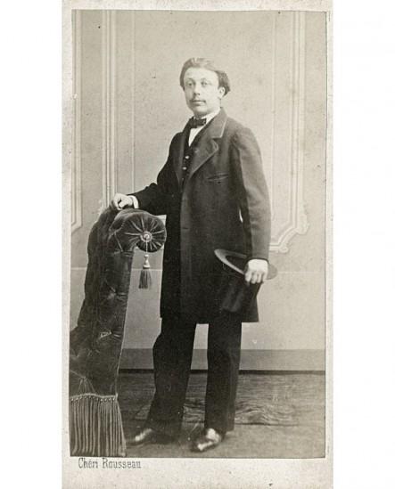 Homme jeune debout, accoudé à un fauteuil, chapeau sous le bras