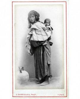 Femme tunisienne un enfant dans le dos, cruche posée à terre.