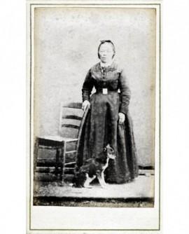 Femme en robe debout, appuyée sur une chaise, un chien assis devant elle