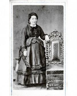 Femme en robe à fronces debout, accoudée à une chaise