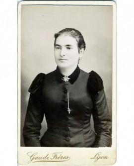 Portrait d'une jeune femme en robe noire à épaulettes renforcées.