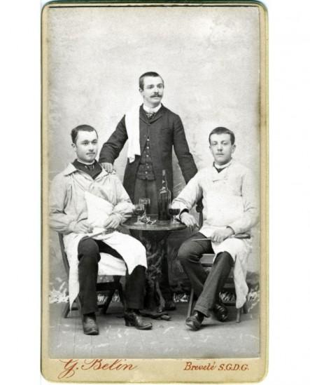 Deux garçons bouchers assis et un garçon de café attablés devant une bouteille et trois verres