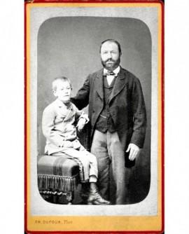 Homme barbu debout, son fils assis sur une chaise