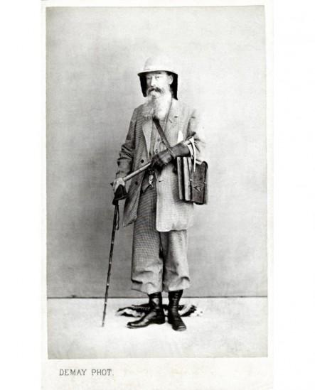 Homme barbu debout en tenue d'expéditio, avec canne, lunette, étui à cartes( M. Schuttlwarth)