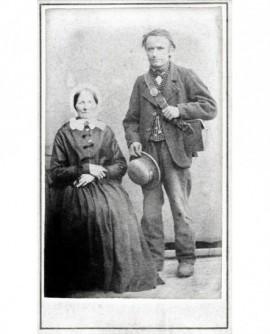Couple : homme debout, sacoche en bandoulière, femme en coiffe assise bras croisés