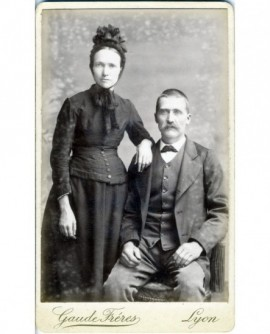 Couple: femme en bonnet debout, appuyée sur l'homme moustachu assis