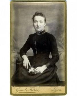 Jeune femme en robe assise, fleur à la main