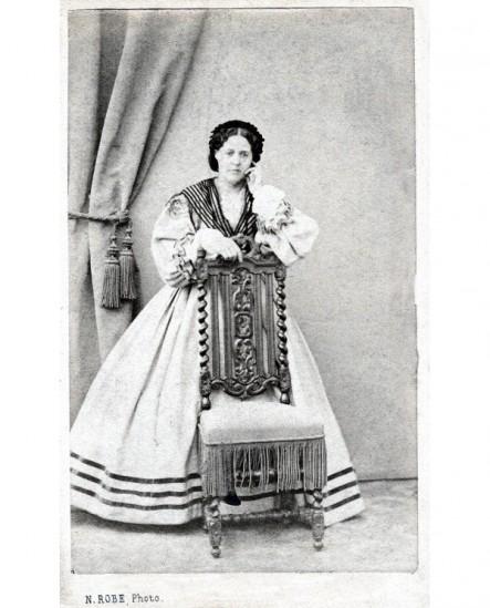 Femme en robe claire à stries noires debout, accoudée à une chaise