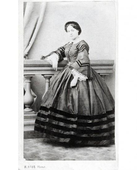 Femme en robe à bandes noires accoudée à une balustrade
