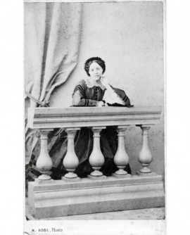 Femme en robe debout, accoudée derrière une balustrade