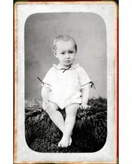 Bébé en chemise assis sur peau de mouton