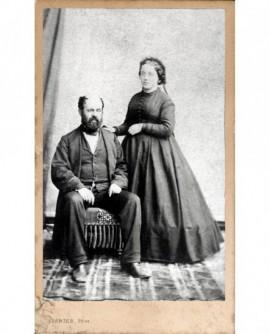 Couple : homme barbu assis, femme debout