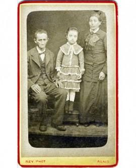 Couple avec leur fille: homme émacié assis, femme et fille debout