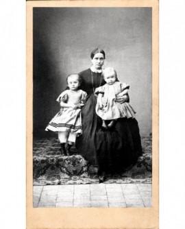 Femme en robe noire assise, deux fillettes dans les bras