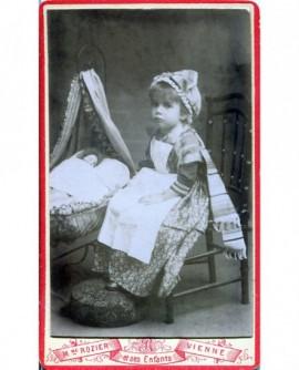 Fillette assise a coté d'un berceau et d'une poupée (jouet)