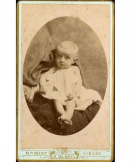 Bébé nu, recouvert d'un drap, assis sur les genoux d'une personne