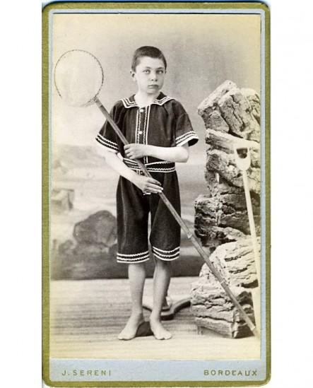 Jeune garçon en tenue de bain, un filet à crevettes à la main