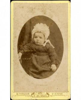 Bébé en bonnet et robe à rayures, assis