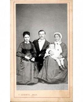 Famille: parents endimanchés et grand-mère en coiffe tenant un garçonnet