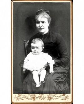 Femme en robe noire, bébé sur les genoux