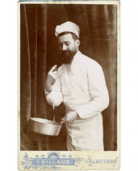 Cuisinier barbu tenant une casserole et goûtant une sauce