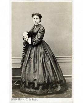 Jeuen femme en robe debout accoudée à une chaise