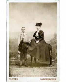 Couple de curistes en excursion: femme en chapeau assise sur un âne, homme debout chapeau à la main.
