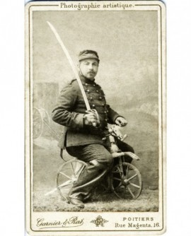 Militaire sabre au clair assis sur cheval de bois