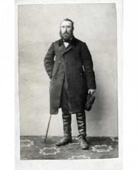 Homme barbu debout en bottes, sa casquette à la main, appuyé sur sa canne