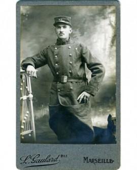Militaire du 53è debout, capote relevée, chien