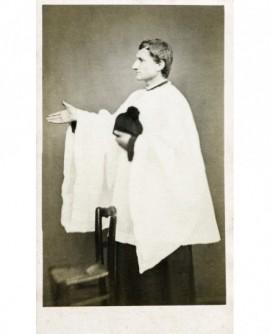 Ecclésiastique en surplis debout, barrette à la main