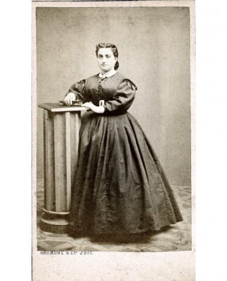 Femme en robe debout, accoudée à une colonne, un livre à la main