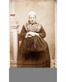 Femme âgée en coiffe assise, mains croisées sur le ventre