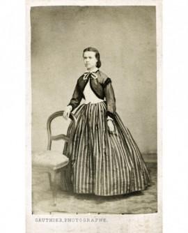 Femme en jupe à rayures et boléro noir debout appuyée à une chaise
