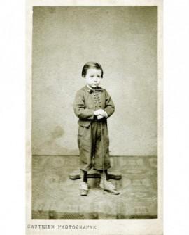 Jeune garçon en costume debout, appuyé sur sa canne