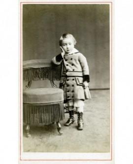 Enfant en manteau et botttines à boutons accoudé à une chaise