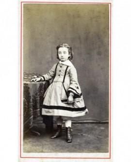 Fillette en robe et bottines debout accoudée à une table