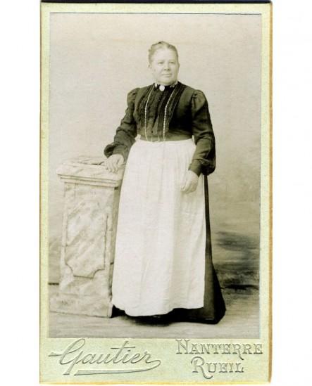 Femme en tablier de cuisinière sur robe noire