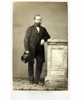 Homme barbu debout, accoudé à une stèle, chapeau à la main