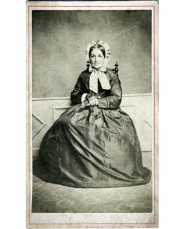 Femme en robe et bonnet assise, mains croisées devant elle