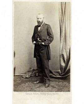 Homme barbu debout, ses deux mains dans ses poches