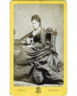 Femme en robe à tournure accoudée à un guéridon