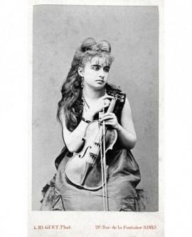 Femme (maquillée) assise tenant un violon