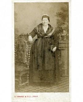 Femme en robe et tablier, appuyée à une chaise, livre